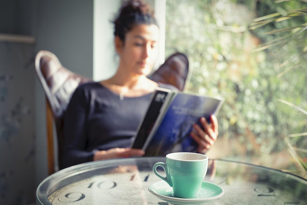 Frau liest Zeitschrift vor Fenster und trinkt Tee